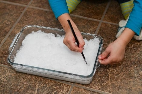 A child using a chopstick to draw in a shallow tray of snow