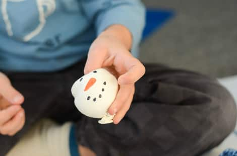 A child's hand squeezing a snowman stress ball