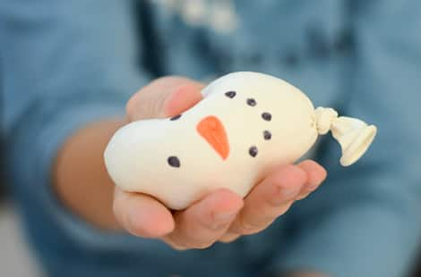 A child squeezing a snowman stress ball