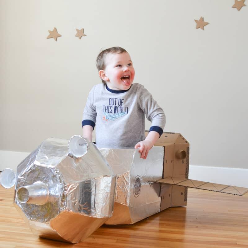 A little boy inside a cardboard Soyuz capsule.