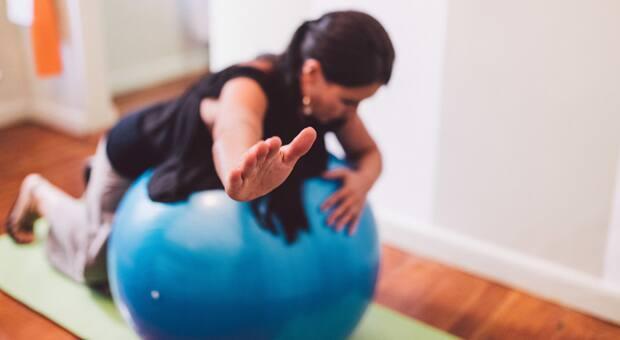 A woman doing pilates on an exercise ball
