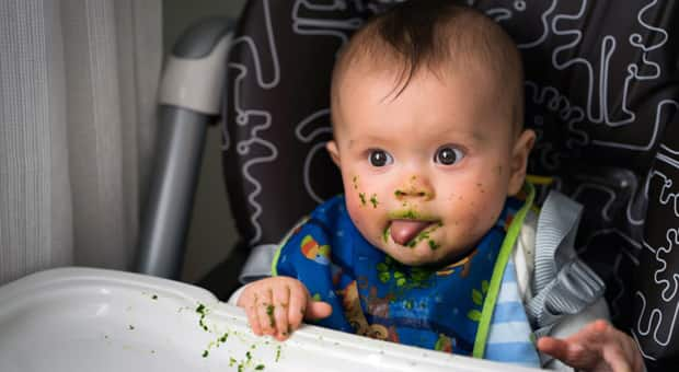 Baby in a high chair covered in food