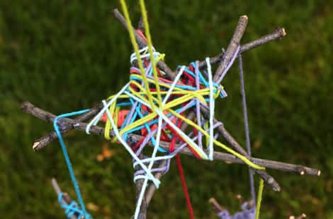 A star covered in multi-coloured yarn with strings hanging from it