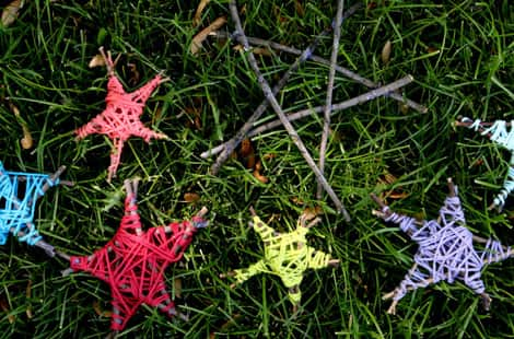 Colourful yarn-covered stars sitting in the grass