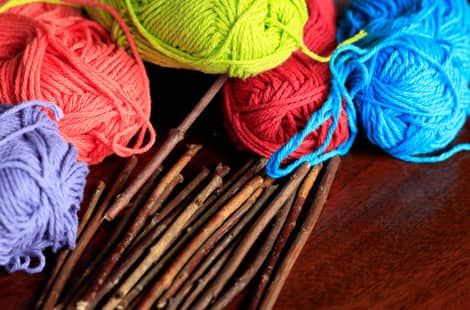 A pile of sticks and balls of colourful yarn sitting on a table