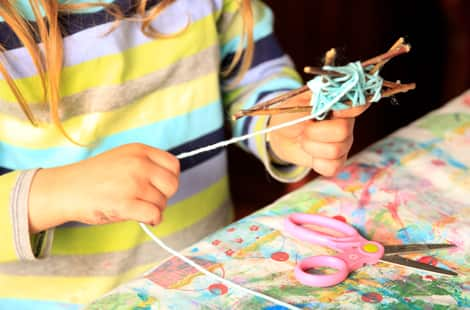A child wrapping a star in yarn