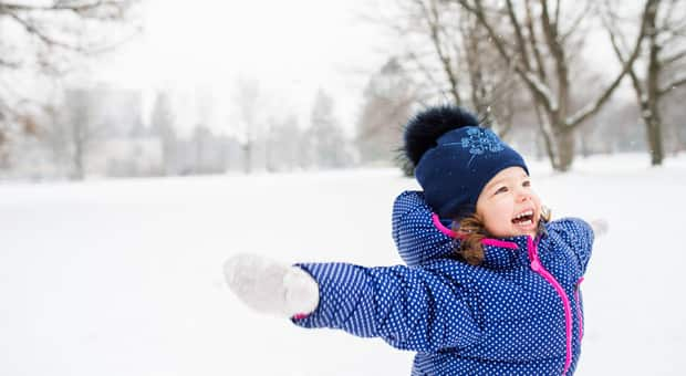 A little girl playing in the snow with her arms open wide