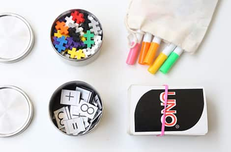 Pens, a card game, a tin full of puzzle pieces and a tin full of magnets.