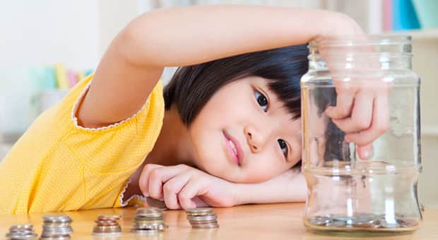 Little girl puts coins in a glass jar.