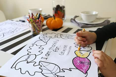 a photo of a kid colouring a placemat