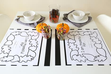 a photo of a table setting with printable colouring mats and crayons laid out for colouring