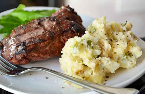 a photo of rustic mashed potatoes on a plate beside a piece of steak