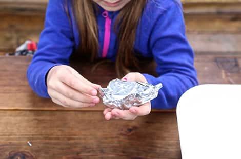 Girl rebuilding tin foil boat.