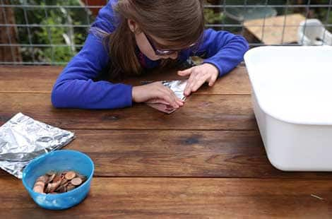 Girl makes a boat using tin foil.