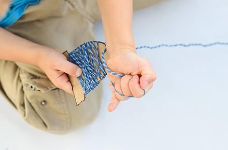 kids hands wrapping cardboard in yarn