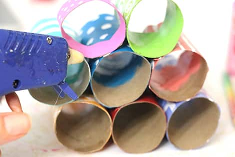 Gluing the painted and decorated rolls together in their arrangement