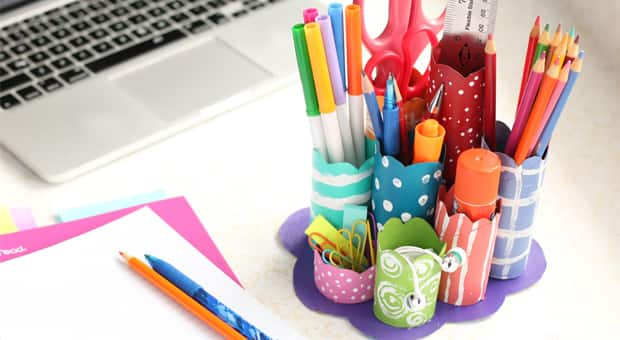 A colourfully painted and decorated toilet paper roll desk caddy holding pens, pencils, highlighters, etc.