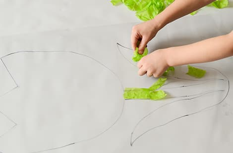 More green tissue paper being paster onto flower traced on contact paper.