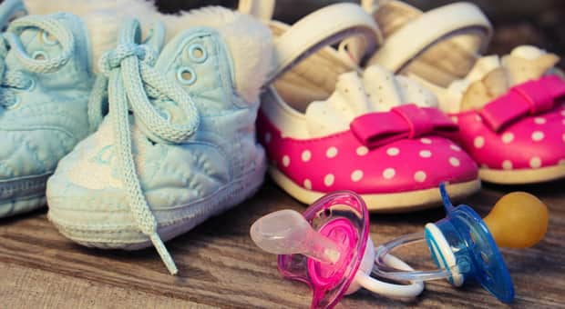 Blue baby shoes beside pink baby shoes with one pink pacifier and one blue one in front