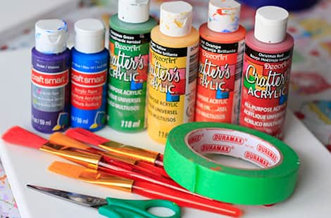 Paints, painter's tape, paintbrushes and scissors.