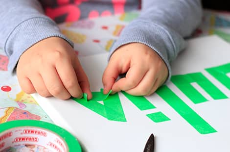 Child's hands are taping painter's tape to her canvas.