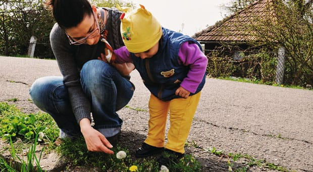A woman and little girl looking at a dandelion