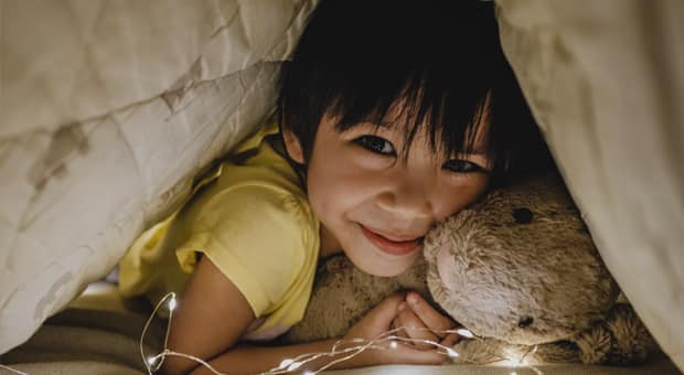 a child smiling and holding their teddy bear