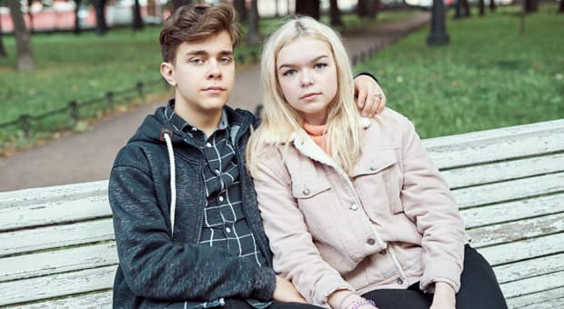 Young couple sitting on a bench and looking at the camera