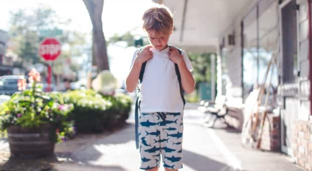 A young boy with a backpack on looking down