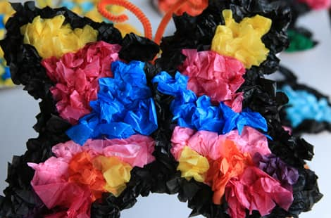 A pink, yellow and blue tissue paper butterfly