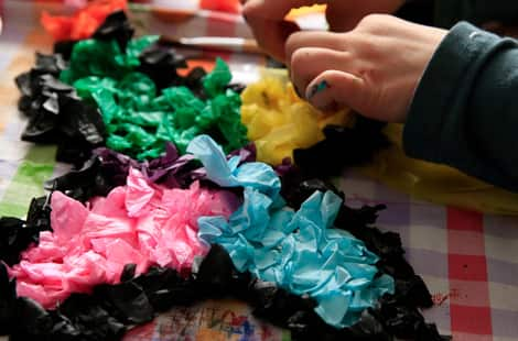 A child gluing crumpled tissue paper to their butterfly design