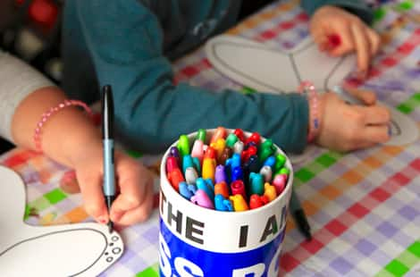 Children working on their tissue paper butterfly designs alongside a bucket of colourful sharpies