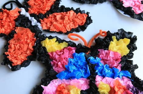 Two tissue paper butterflies, one covered in orange tissue paper, the second in blue, yellow and pink