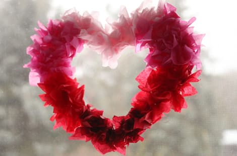 A tissue paper heart hanging in front of a window