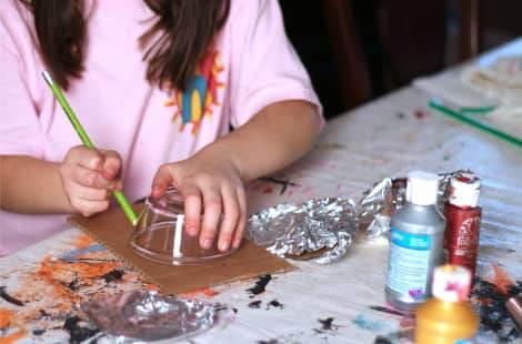 A little girl tracing a circle on cardboard