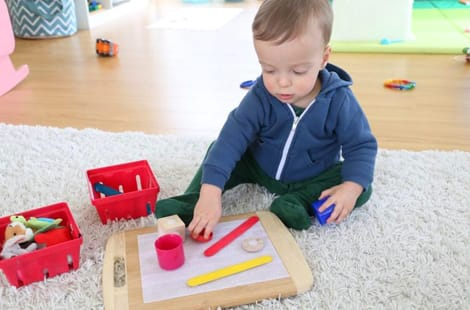A little boy sticking items to the velcro board