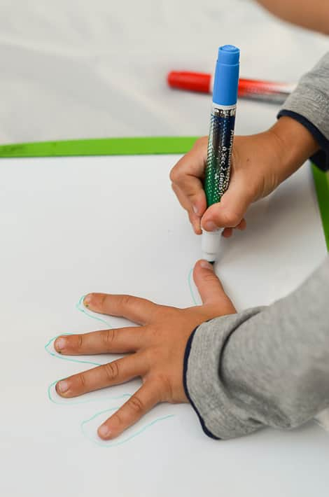 a photo of a child's hand that is being traced on a whiteboard
