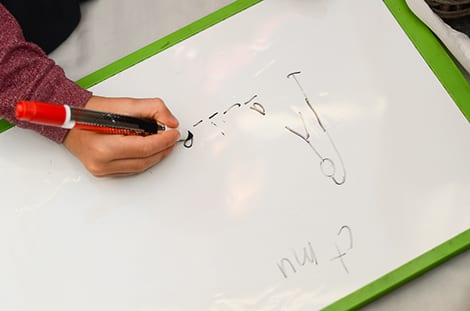 a photo of a child drawing on a whiteboard playing hangman