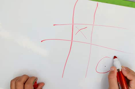 a photo of a child drawing on x's and o's on a white board