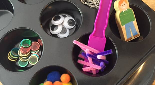 Muffin tin full of various supplies like googley eyes, plastic bingo chips and paper clips.