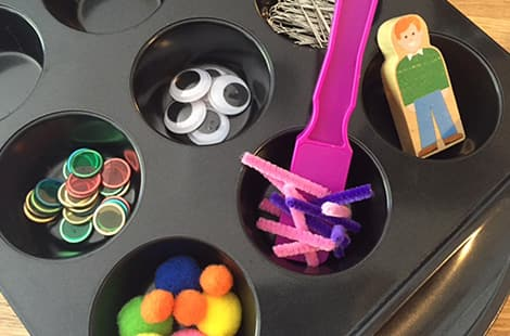 Muffin tin with googly eyes, bingo markers and paper clips.