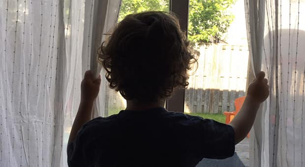 Child holds window curtains to look outside.
