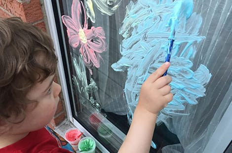 Child paints colourful art on window.