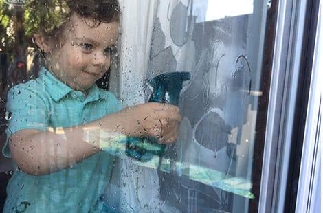 Toddler washing windows.