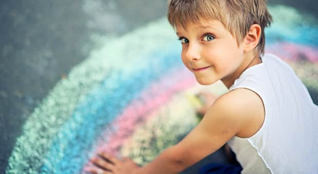 A little boy in front of a chalk drawing of a rainbow