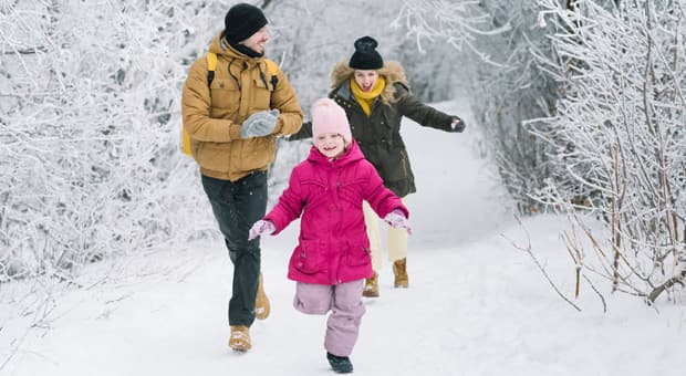 A family playing in the snow on a hike