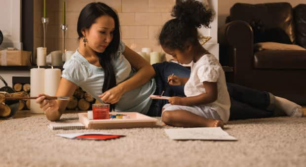 A mother and her daughter sitting on the ground and painting pictures