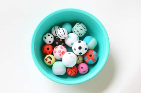 A colourful bowl of painted and decorated wooden beads