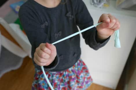 A child holding onto each end of the fabric strip and pulling