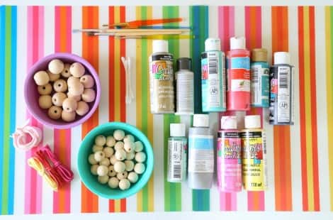 A rainbow place mat with materials on top: two bowls of wooden beads, cotton swabs, paintbrushes, a variety of paint bottles and colourful thread